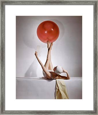 A Model Balancing A Red Ball On Her Feet Framed Print by Horst P Horst