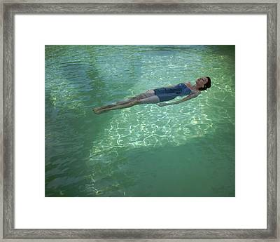 A Model Floating In A Swimming Pool Framed Print