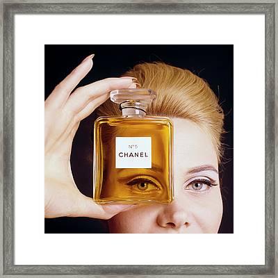 A Model Holding A Bottle Of Perfume Framed Print