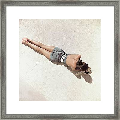A Model Lying Down Wearing A Play Suit Framed Print by John Rawlings