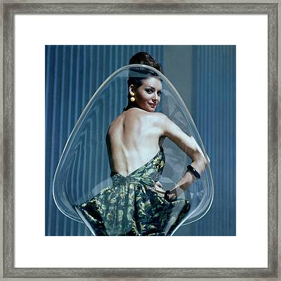 A Model Posing On A Transparent Bucket Chair Framed Print by  Leombruno-Bodi