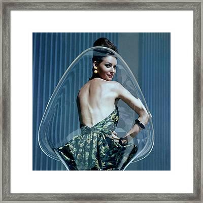 A Model Posing On A Transparent Bucket Chair Framed Print