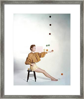 A Model Sitting On A Stool Juggling Framed Print
