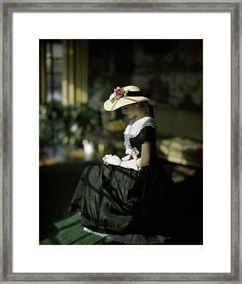 A Model Wearing A Black Dress And Sun Hat Framed Print by John Rawlings