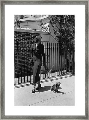 A Model Wearing A Dress Walking A Dog Framed Print