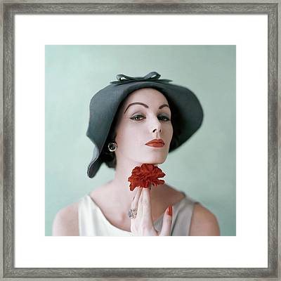 A Model Wearing A Hat And Holding A Flower Framed Print by Karen Radkai