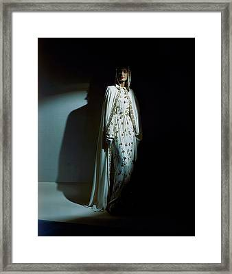 A Model Wearing A Hooded Ivory Cape Over An Ivory Framed Print