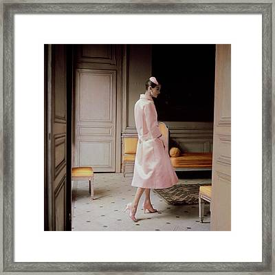 A Model Wearing A Pink Coat Framed Print by Karen Radkai