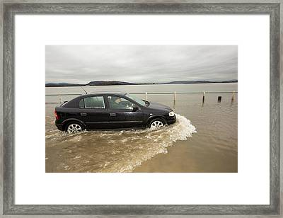 A Motorist Travels Through Flood Waters Framed Print by Ashley Cooper