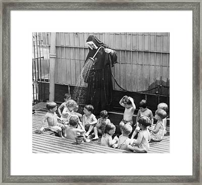 A Nun Watering Children Framed Print by Underwood Archives