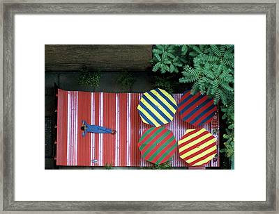 A Patio With Striped Umbrellas Framed Print