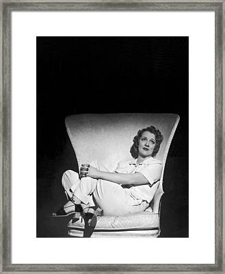 A Pensive Woman Curled Up In A Chair Framed Print