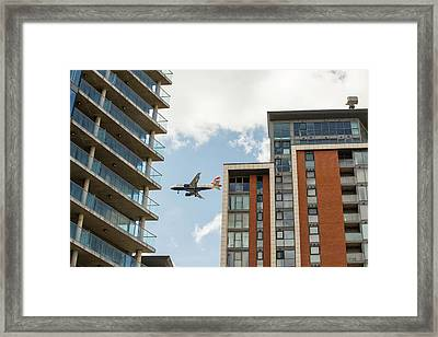 A Plane Flying Past Apartment Blocks Framed Print by Ashley Cooper