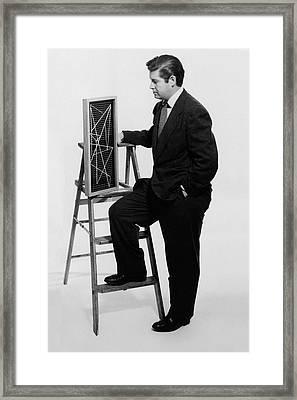 A Portrait Of Paul Mccobb Leaning On A Ladder Framed Print