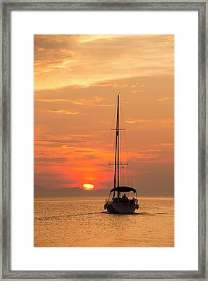 A Sailing Boat At Sunset Framed Print by Ashley Cooper