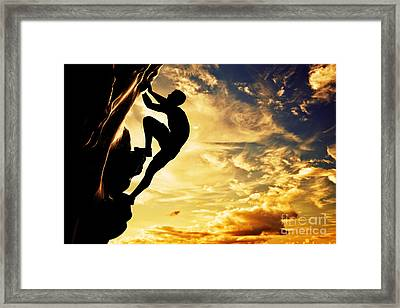A Silhouette Of Man Free Climbing On Rock Mountain At Sunset Framed Print
