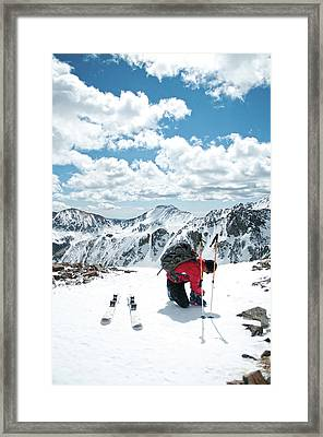A Skier Buckles His Boots On The Summit Framed Print