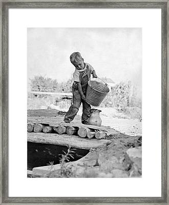 A Small Boy On A Farm Pours Water From A Bucket Into A Pitcher F Framed Print by Underwood Archives