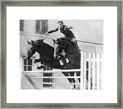 A Stunt Rider On Two Horses. Framed Print by Underwood Archives