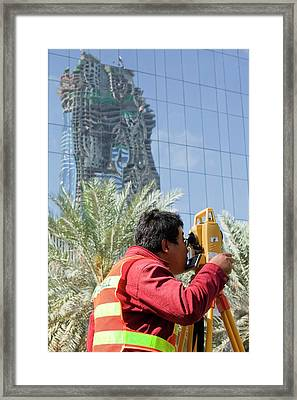 A Surveyor On A Construction Project Framed Print by Ashley Cooper