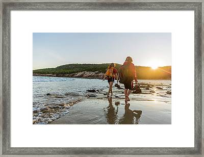 A Teenage Boy And Girl Walk On Sand Framed Print