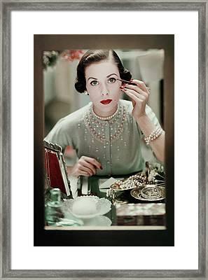 A Woman Applying Make-up Framed Print