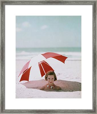 A Woman Buried In Sand At A Beach Framed Print