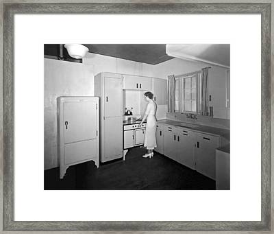 A Woman In Her Kitchen Framed Print by Underwood Archives