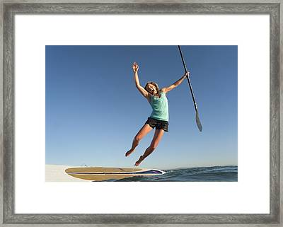 A Woman Jumps Into The Water Off A Surf Framed Print