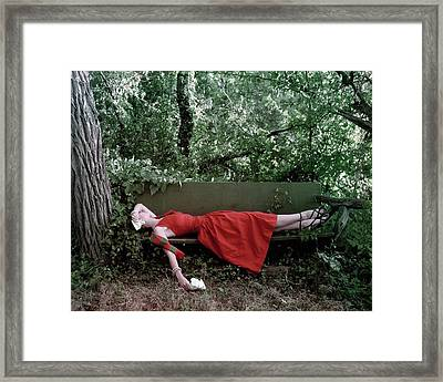 A Woman Lying On A Bench Framed Print by John Rawlings