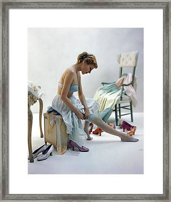 A Woman Putting On Her Stockings Framed Print by John Rawlings
