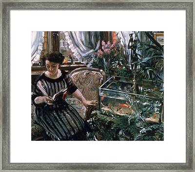 A Woman Reading Near A Goldfish Tank Framed Print