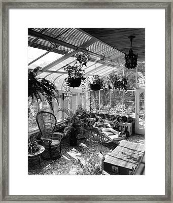 A Woman Resting On A Chair Inside A Greenhouse Framed Print