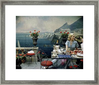 A Woman Sitting At A Dining Table In Front Framed Print