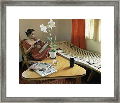 A Woman Sitting By A Coffee Table And Chaise Framed Print