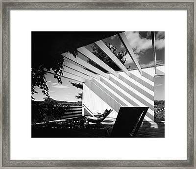 A Woman Sitting On A Reclining Chair On A Rooftop Framed Print by Robert M. Damora