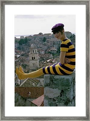 A Woman Sitting On A Stone Wall Framed Print