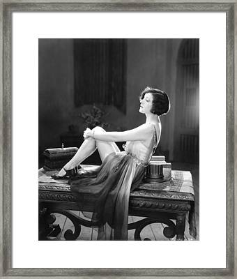 A Woman Sitting On A Table Framed Print by Underwood Archives