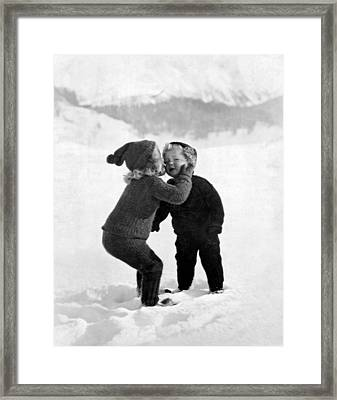 A Young Girl Gives Her Little Brother A Kiss On The Cheek In The Snow Framed Print