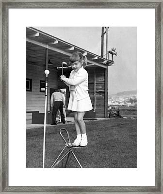 A Young Girl Hits A Golf Ball Framed Print by Underwood Archives