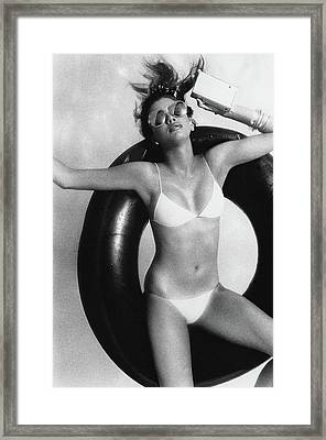 A Young Woman Floating On An Inner Tube Framed Print