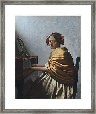 A Young Woman Seated At The Virginal Framed Print by Johannes Vermeer