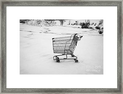 abandoned shopping cart in snow covered supermarket parking lot Saskatoon Saskatchewan Canada Framed Print