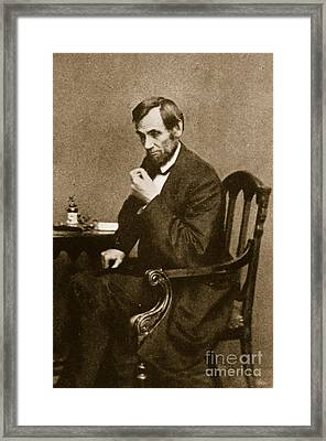 Abraham Lincoln Sitting At Desk Framed Print by Mathew Brady