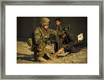Airman Provides Medical Aid To A Local Framed Print by Stocktrek Images