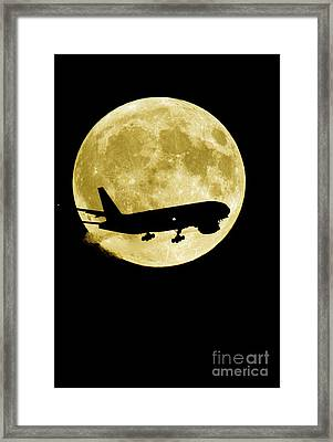 Airplane Silhouetted Against A Full Moon Framed Print by David Nunuk