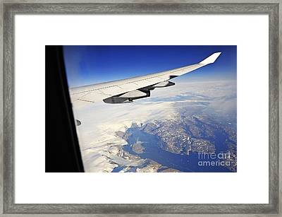Airplane Wing Over Snowy And Rocky Coastline Framed Print by Sami Sarkis