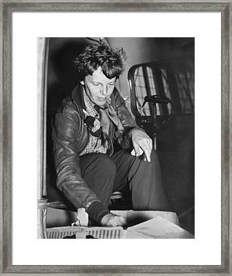 Amelia Earhart Checks Supplies Framed Print by Underwood Archives