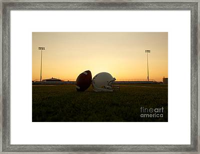American Football And Helmet On The Field At Sunset Framed Print