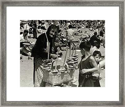 An Elderly Woman Selling Food On The Beach Framed Print by Lusha Nelson